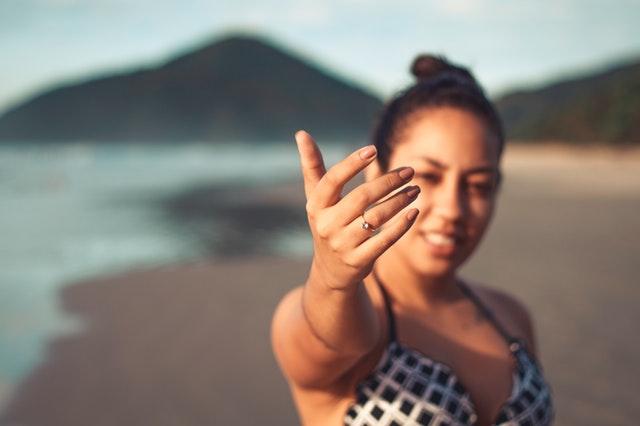 Žena ukazujúca ruku s diamantovým prsteňom