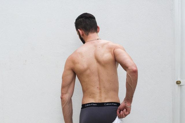 Svalnatý muž v spodnej bielizni otočený chrbtom.jpg