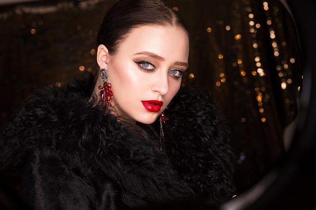 Žena v čiernom kabáte s výraznými náušnicami s červenými kameňmi