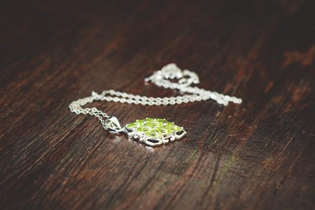 Strieborný  náhrdelník so zeleným kaňom na drevenom stole