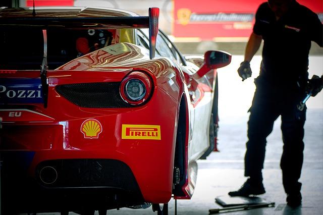 Muž v servise stojí pri červenom aute.jpg