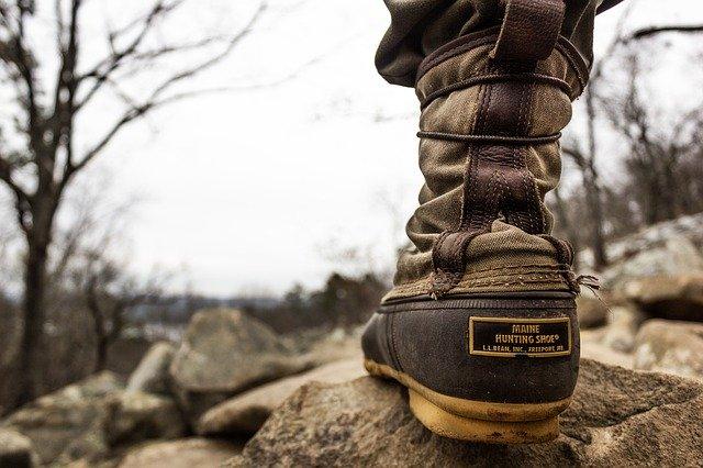 Detail na nohu v turistickej obuvi na skale v prírode.jpg