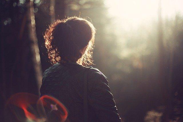 Žena v zelenej bunde pozerá do slnka.jpg