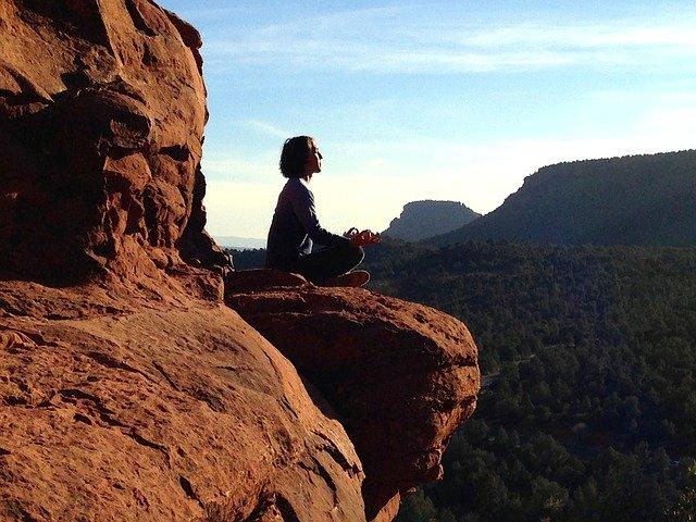 Žena sedí v tureckom sede na skale a medituje.jpg