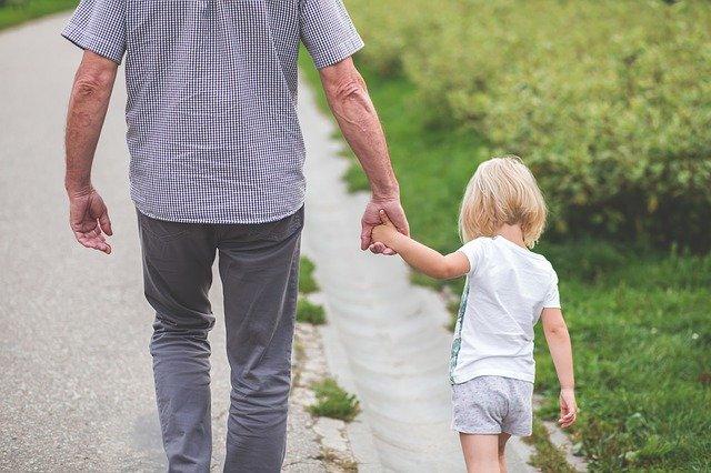 Starší muž kráča po chodníku a drží za ruku vnučku.jpg
