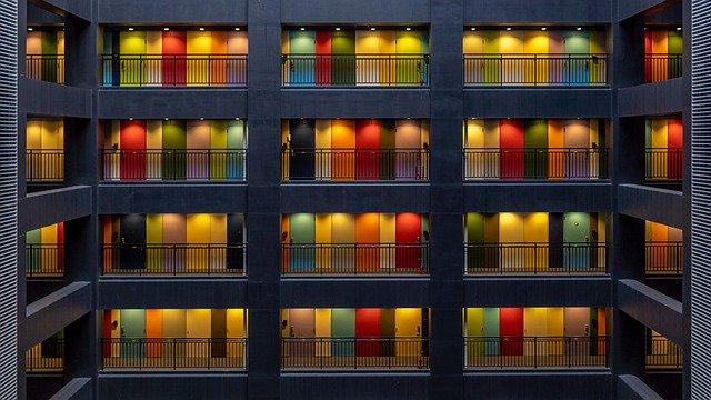 Poschodová budova s množstvom farebných dverí a balkónov